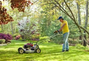caucasian man in a hat mowing the lawn