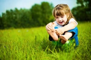 girl playing with her foot in a field